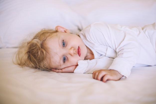 Европейский маленький ребенок, лежащий на кровати. белый, грустный, красивый, мальчик, девочка