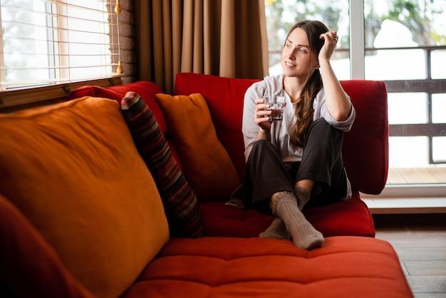 유럽의 웃는 소녀는 소파에 앉아 집에서 유리로 물을 마신다. 사려깊은 젊은 여성은 평상복을 입는다. 현대 아파트의 거실 인테리어입니다. 낮