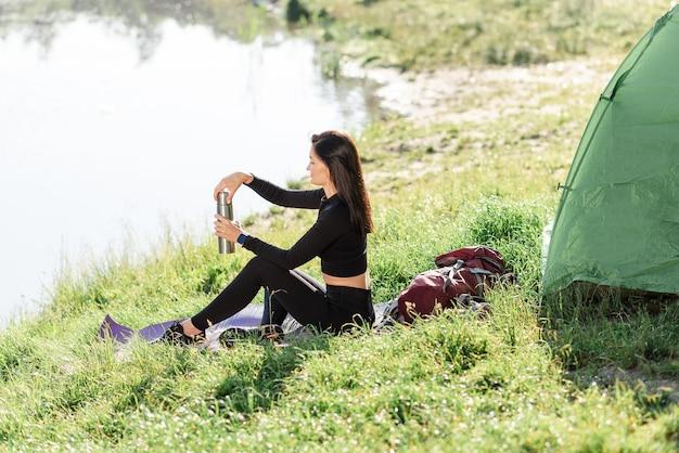 ヨーロッパのスポーツの女の子はテントの近くのフィットネスマットに座ってお茶を飲みます。緑の牧草地。若いきれいな女性はスポーツウェアを着て、日光を楽しんでいます。自然の休息と観光の概念。キャンプ休暇