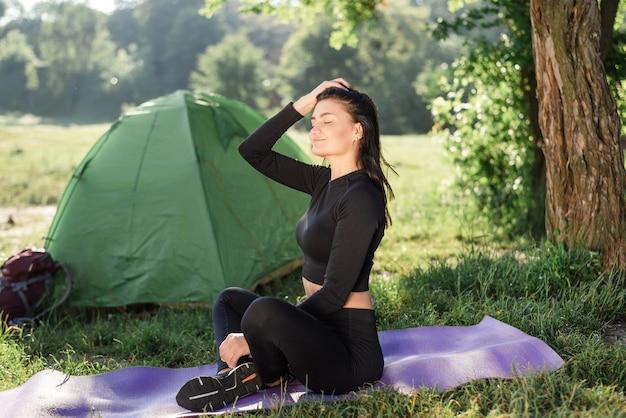 テントの近くのフィットネスマットに座って日光を楽しんでいるヨーロッパのスポーツの女の子。緑の牧草地。若い魅力的な女性はスポーツウェアを着用します。自然の休息と観光の概念。キャンプ休暇。晴れた日
