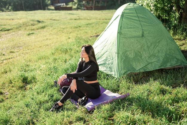テントの近くのフィットネスマットに座って日光を楽しんでいるヨーロッパのスポーツの女の子。緑の牧草地。若い美しい女性はスポーツウェアを着用します。自然の休息と観光の概念。キャンプ休暇。晴れた日