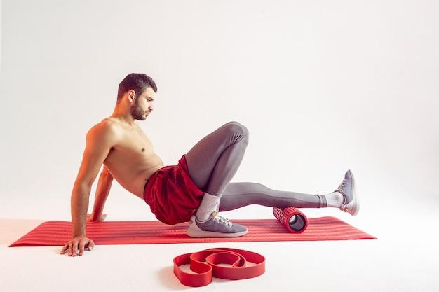 Европейский спортсмен делает упражнения с массажным роликом на фитнес-коврике. молодой сосредоточенный красавец бородатый с обнаженным спортивным торсом. изолированные на бежевом фоне. студийная съемка. копировать пространство