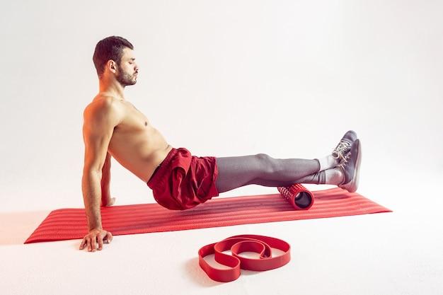 Европейский спортсмен делает упражнения с массажным роликом на фитнес-коврике. молодой сосредоточенный красавец бородатый мужчина с обнаженным спортивным торсом. изолированные на бежевом фоне. студийная съемка. копировать пространство