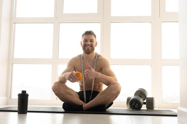 유럽 스포츠맨은 피트니스 매트에 앉아 오렌지색을 들고 엄지손가락 제스처를 보여줍니다. 벌거 벗은 몸통을 가진 젊은 웃는 남자. 신체 그림 관리의 개념입니다. 현대적인 햇살 가득한 넓은 아파트의 인테리어