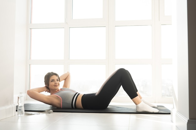 European sportswoman doing crunching for abdominal muscles on fitness mat. young beautiful woman wear sportswear. concept of sport activity at home. interior of modern spacious apartment. sunny day