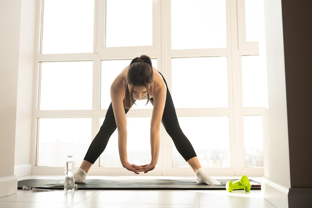 European sportswoman doing exercise and stretching on fitness mat. young pretty woman wear sportswear. concept of sport activity at home. interior of modern spacious apartment. sunny day