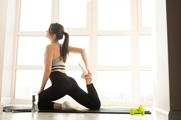 European sportswoman doing exercise and stretching on fitness mat. young woman with closed eyes wear sportswear. concept of sport activity at home. interior of modern spacious apartment. sunny day