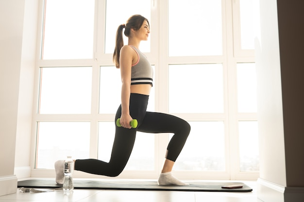European sportswoman doing lunges for legs on fitness mat. young beautiful smiling woman wear sportswear. concept of sport activity at home. interior of modern spacious apartment. sunny day