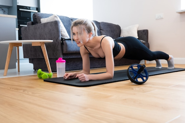European sportswoman doing plank for abdominal muscles on fitness mat. young beautiful smiling blonde woman wear sportswear. concept of sport activity at home. interior of studio apartment