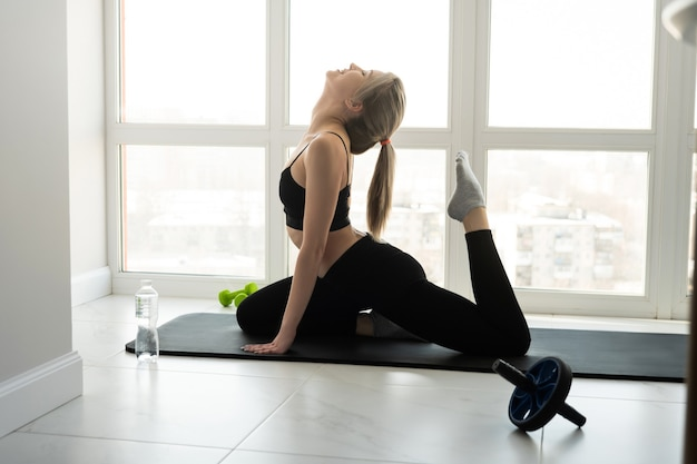 European sportswoman do exercise on fitness mat. side view of young blonde woman with closed eyes wear sportswear. concept of sport activity at home. interior of modern spacious apartment. sunny day