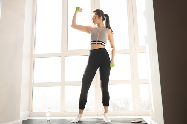 European sportswoman do exercise for shoulder with dumbbell on fitness mat. young beautiful woman wear sportswear. concept of sport activity at home. interior of modern spacious apartment. sunny day