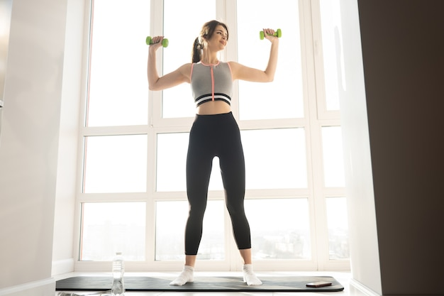European sportswoman do exercise for shoulders with dumbbells on fitness mat. young smiling woman wear sportswear. concept of sport activity at home. interior of modern spacious apartment. sunny day