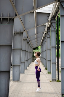 Европейская спортсменка прыгает на скакалке. кирпичная площадка под крышей стадиона. вид сбоку молодой красивой девушки носить спортивную одежду и кроссовки. понятие о спорте на открытом воздухе. летний солнечный день