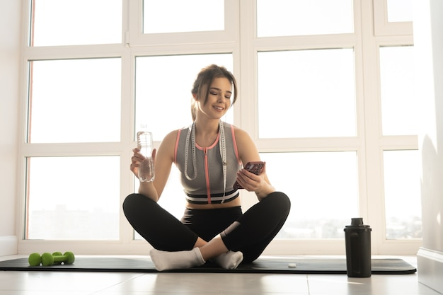 European sportswoman sit on fitness mat and use mobile phone at home. young woman wear sportswear and hold bottle with water. concept of body figure care. interior of spacious apartment. sunny day