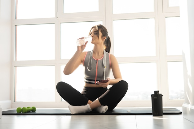 European sportswoman sitting on fitness mat and drinking water from bottle at home. young beautiful woman wear sportswear. concept of body figure care. interior of modern spacious apartment. sunny day