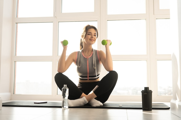 European sportswoman sitting on fitness mat and holding dumbbells at home. young beautiful smiling woman wear sportswear. concept of body figure care. interior of modern spacious apartment. sunny day