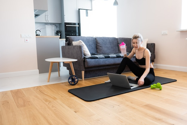 European sportswoman sitting on fitness mat and watching something on laptop computer. young beautiful smiling blonde woman wear sportswear and holding bottle with water. interior of studio apartment