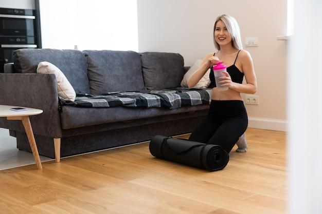유럽 스포츠우먼은 바닥에 앉아서 집에서 물을 여는다. 젊고 아름다운 웃는 금발의 여성은 운동복을 입는다. 집에서 스포츠 활동의 개념입니다. 스튜디오 아파트의 인테리어