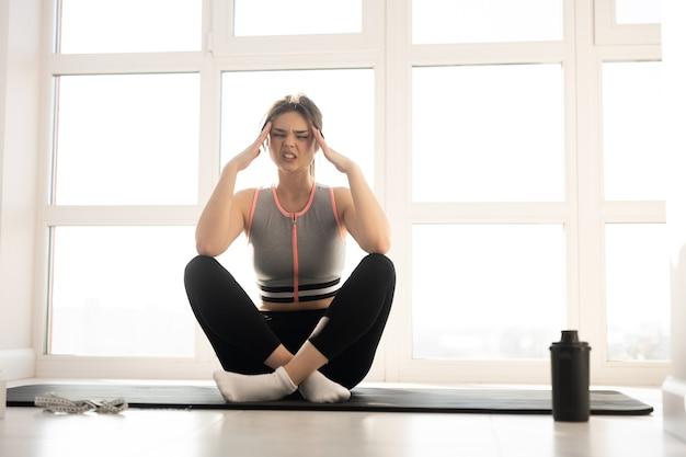 フィットネスマットの上に座って頭痛を持つヨーロッパのスポーツウーマン。若い美しい女性はスポーツウェアを着用します。家庭でのスポーツ活動の概念。モダンで広々としたアパートメントのインテリア。晴れた日