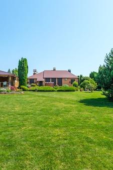 Вилла в европейском стиле и сад с красиво подстриженными кустами и деревьями