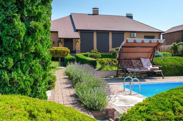 Вилла в европейском стиле с бассейном и садом с красиво подстриженными кустами и камнями перед домом. ландшафтный дизайн. фото высокого качества