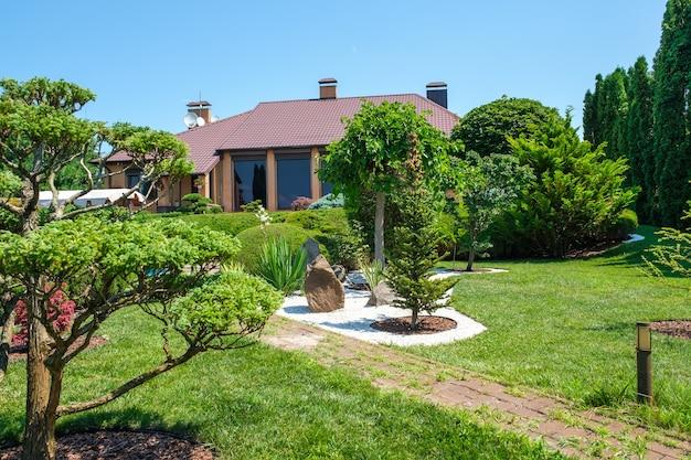 Вилла в европейском стиле с бассейном и садом с красиво подстриженными кустами и деревьями перед домом. ландшафтный дизайн. фото высокого качества