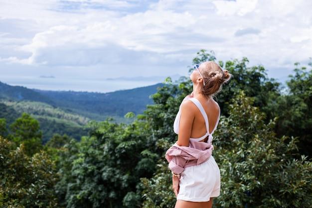 Европейская стильная женщина-блогер-турист стоит на вершине горы с удивительным тропическим видом на остров самуи. таиланд. мода на открытом воздухе портрет женщины.