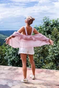 ヨーロッパのスタイリッシュな女性ブロガーの観光客は、サムイ島タイの素晴らしい熱帯の景色を望む山の頂上に立っています女性のファッション屋外ポートレート