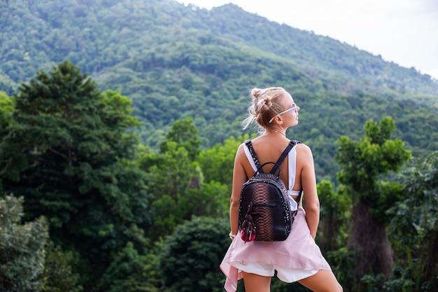 Turista di blogger donna elegante europea si trova sulla cima della montagna con incredibile vista tropicale dell'isola di koh samui thailandia moda ritratto all'aperto di donna
