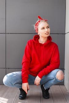 청바지에 검은 부츠에 빈티지 두건에 유행 빨간 후드 티에 유럽의 세련된 젊은 금발의 여자는 여름 날에 회색 건물 근처에 앉아있다
