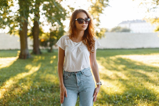 녹색 나무 사이 공원에서 포즈 유행 선글라스에 흰색 티셔츠에 유행 청바지에 유럽의 세련 된 젊은 힙 스터 여자