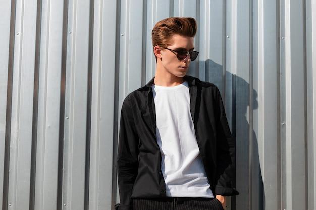 유행 선글라스에 우아한 옷에 유행 헤어 스타일을 가진 유럽의 세련 된 젊은 남자는 화창한 날에 도시의 빛나는 금속 벽 근처 포즈. 잘 생긴 hipster 남자는 태양을 즐긴다. 신사복.
