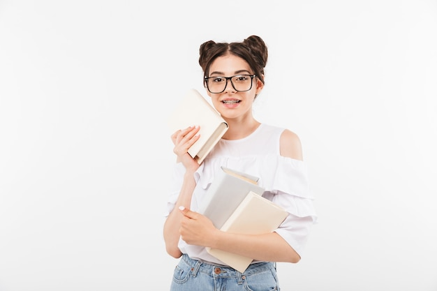 European teenage girl with double buns hairstyle and dental braces smiling and holding many studying books, isolated on white