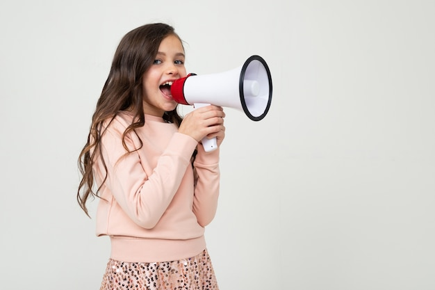 European teenager girl with a megaphone stands sideways on a white studio background with copy space.