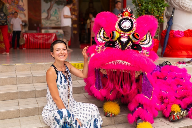 A european tourist girl at a chinese new year celebration in a chinese temple is photographed with a traditional chinese dragon. festive chinese entertainment