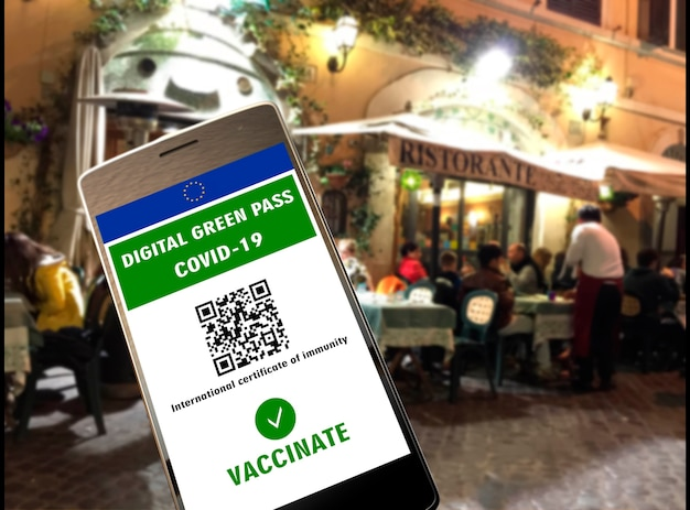 Цифровой зеленый пропуск европейского союза с qr-кодом на экране мобильного телефона, фоне открытого ресторана. covid-19 иммунитет. путешествуйте без ограничений.