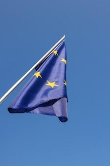 유럽 연합 eu 깃발이 유럽 애국심의 상징인 맑고 푸른 하늘 위에 깃대에 매달려 있으며 낮은 각도, 측면 전망