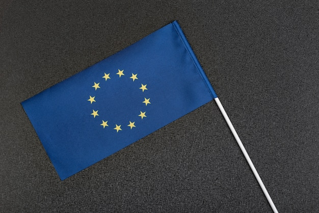 European union flag on a black background. small blue flag with stars