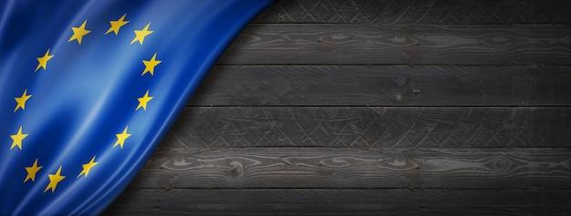 European union flag on black wood wall. horizontal panoramic banner.