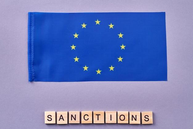 欧州連合の旗。木製の立方体で作られた制裁の言葉。