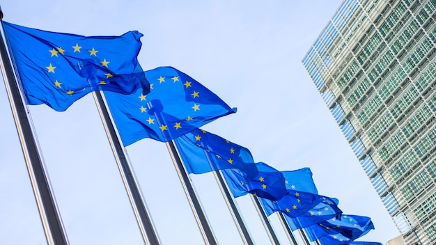 Флаги европейского союза перед зданием берлемон в брюсселе, бельгия