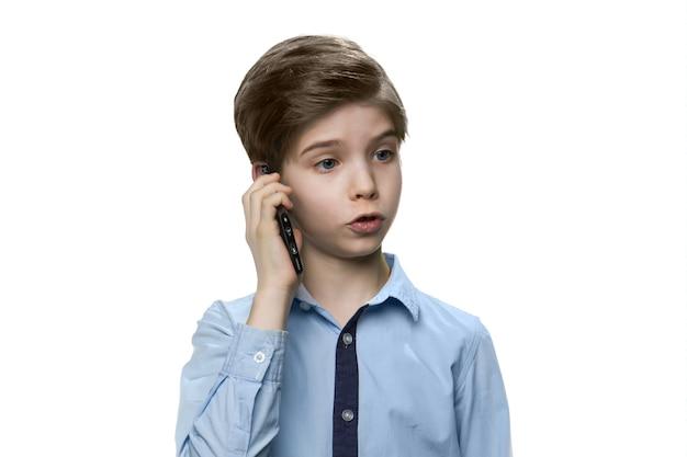 Европейский белый мальчик в синей рубашке разговаривает по смартфону на белой стене
