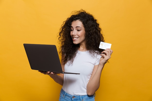 Европейская женщина 20 лет в повседневной одежде держит черный ноутбук и кредитную карту, изолированную на желтом