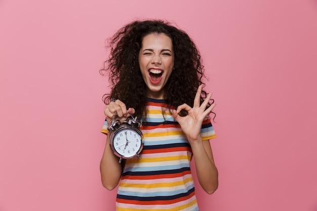 ピンクで隔離の目覚まし時計を保持している巻き毛のヨーロッパの女性20代