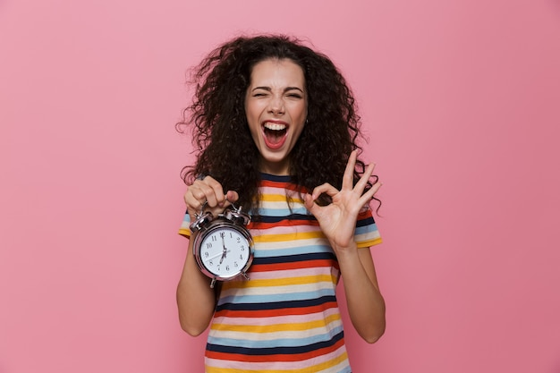 European woman 20s with curly hair holding alarm clock isolated on pink