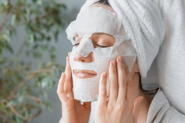 ヨーロッパの女性が顔のスキンケアとスパトリートメントに白い布の保湿マスクを適用します