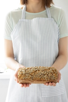 自家製サワードウを保持している軽いエプロンでそばパン白人女性を保持しているヨーロッパの女性パン屋