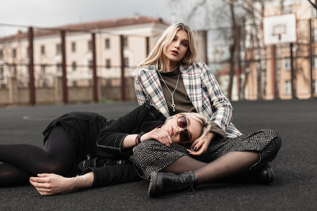 European woman blond in fashion sunglasses in casual clothes lies on friend stylish checkered youth blazer in retro-style