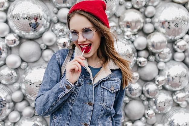 Donna europea in giacca di jeans in posa giocosamente con lecca-lecca. ragazza estatica con capelli castano chiaro che tiene la caramella sulla parete della scintilla.