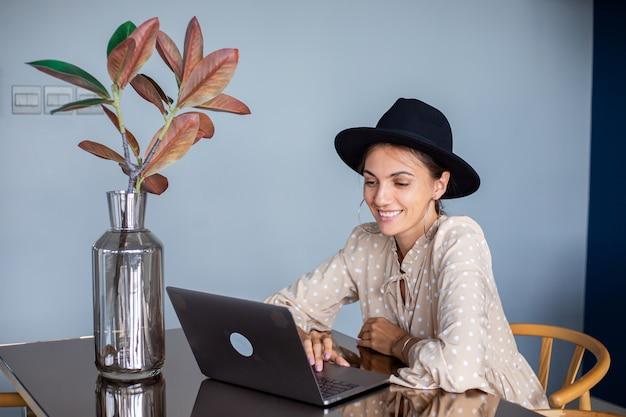 Donna europea in abito e cappello classico lavora a casa in cucina